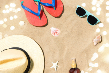 vacation, travel and summer holidays concept - straw hat, flip flops, sunglasses and sunscreen oil...