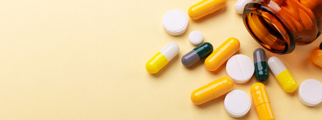 Multicolor tablets and pills capsules from glass bottle on yellow background Health care Close-up Horizontal banner Copy space