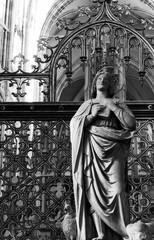 Stone statue of female saint  - black and white photo