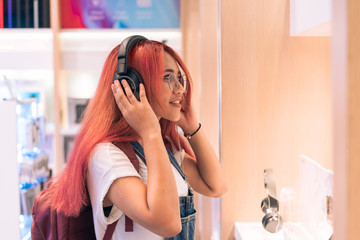Tuinposter Muziekwinkel Asian social influencer woman trying on headphones inside retail store - Happy millennial diverse girl shopping and testing lifestyle music tech products - Technology, electronic and purchase concept.