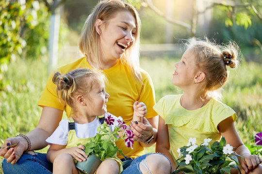 Young children in yellow playing with mom in the garden on a sunny day. They help to plant sprouts and take care of nature. Sisters are smiling and hugging their mother. Happy family