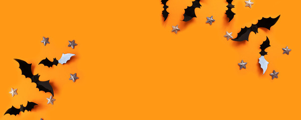 Fototapeta Halloween flat lay composition of black paper bats fly up and gold stars on an orange background obraz