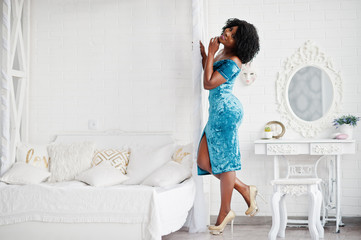 Afican american women in brilliant glitter sequins turqoise dress posed at white room against mirror with bed.