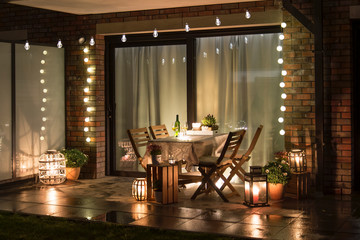 Summer evenig terrace with candles, wine and lights, after rain