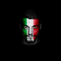 Flag of Italy painted on a face of a man on black background.