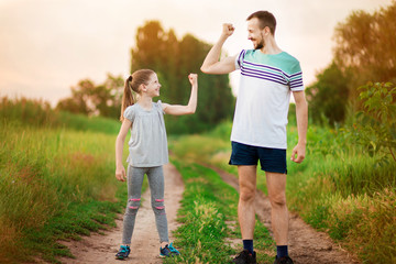 Full length portrait of handsome father and his cute little daughter showing their muscles, looking at camera and smiling outdoor at sunset