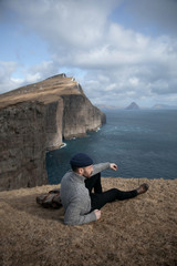 Young man sitting on top of a cliff in Faroe Islands