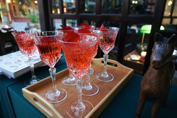 Red Cocktail in fancy glasses on wood plate and table in at restaurant