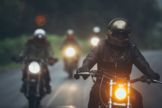 A group of motorcyclists are traveling on the rainy highway.