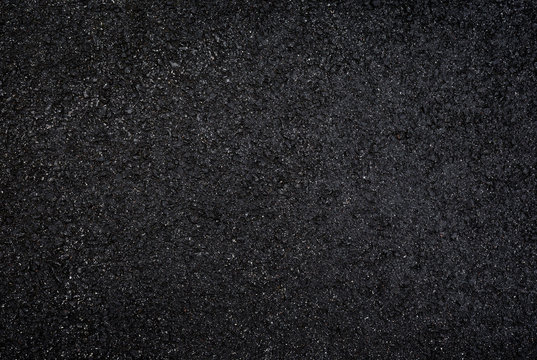 High resolution full frame textured dark background of wet, black asphalt, viewed from above.