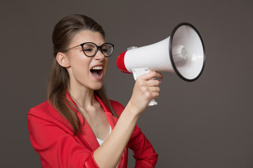 business woman shouting at a megaphone. Young pretty girl in glasses and a red jacket
