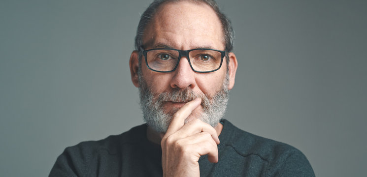 Portrait of a bearded mature adult casual Businessman with glasses looking into camera