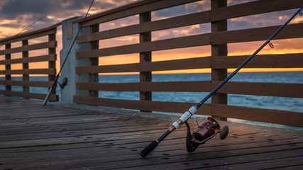 Lone red fishing pole on Juno Beach, Florida pier at sunrise