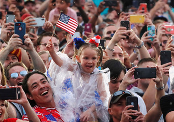 """A child waves flags as people take photos while U.S. President Donald Trump and first lady Melania Trump arrive for the """"Salute to America"""" event during Fourth of July Independence Day celebrations at the Lincoln Memorial in Washington"""