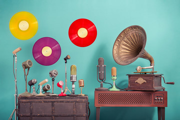 Old retro microphones, antique gramophone phonograph turntable with brass horn, flying multicolor LP vinyl record discs front blue background. Nostalgia music concept. Vintage style filtered photo