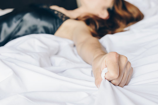 Woman hand pulling and grab bed sheet, sign of orgasm.