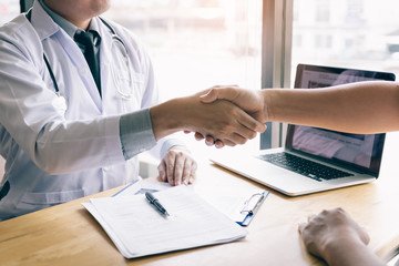 Dentist agreed with the patient by holding shaking hands with confidence.