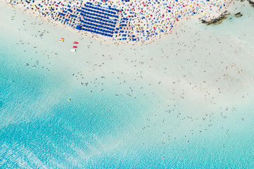 Wall Mural - Stunning aerial view of the Spiaggia Della Pelosa (Pelosa Beach) full of colored beach umbrellas and people sunbathing and swimming in a beautiful turquoise clear water. Stintino, Sardinia, Italy.