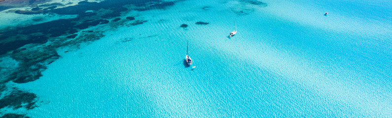 View from above, stunning aerial view of some boats sailing on a beautiful turquoise clear water. Spiaggia La Pelosa (Pelosa beach) Stintino, Sardinia, Italy.