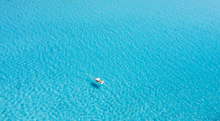 Wall Mural - View from above, stunning aerial view of an inflatable boat with tourists on board sailing on a beautiful turquoise clear water. Spiaggia La Pelosa (Pelosa beach) Stintino, Sardinia, Italy.