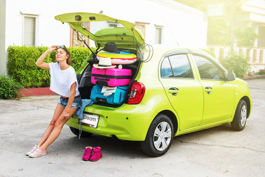 Ready to travel. Woman in green car before trip