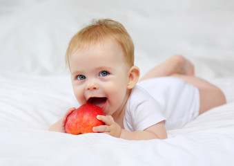 Charming blue-eyed baby 7 months lying in bed in white clothes with red apples