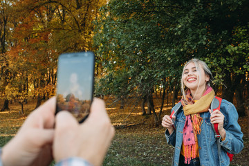 Fall hiking. Man using smartphone camera to take picture of his girlfriend on autumn forest background.