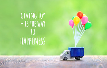 giving joy is the way to happiness - inspiration motivation quote. colorful air balloons and truck toy on wood background. Concept for visualization of delivery services, logistics, business, travel