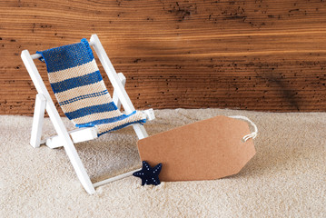 Summer Label With Sand And Aged Wooden Background. Copy Space For Advertisement Or Free Text. Deck Chair For Holiday Or Vacation Feeling.