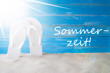 German Text Sommerzeit Means Summer Time. Sunny Summer Greeting Card With Sand And Flip Flops. Blue Vintage And Shabby Chic Wooden Background.