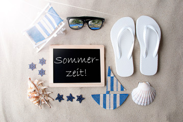 Flat Lay Of Chalkboard On Sandy Background. Sunny Summer Decoration As Holiday Greeting Card. Sand And Beach Environment. German Text Sommerzeit Means Summertime