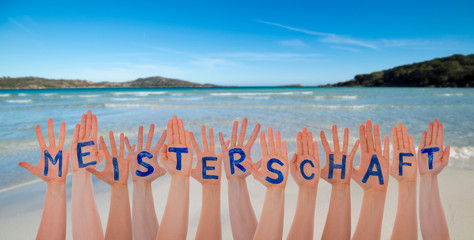 Many Hands Building German Word Meisterschaft Means Championship. Beautiful Beach, Ocean And Sea As Background