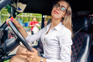 girl in glasses sitting in a car audio show close up