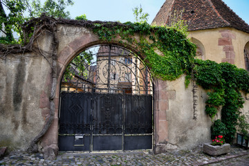 Wrought iron gate as entrance to a larger courtyard in Alsace in France.