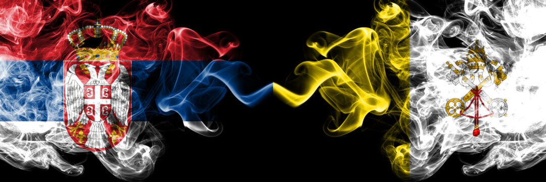 Serbia vs Vatican city smoky mystic flags placed side by side. Thick colored silky smokes combination of Serbian and Vatican city flag