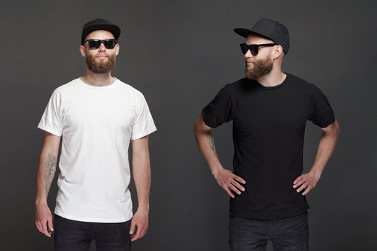 Hipster handsome male model with beard wearing white blank t-shirt and a baseball cap with space for your logo or design in casual urban style.