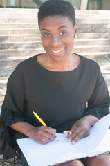 Cheerful African American woman drawing outside. Happy black lady sitting on stairs, holding color pencils and open album and smiling at camera. Craft concept