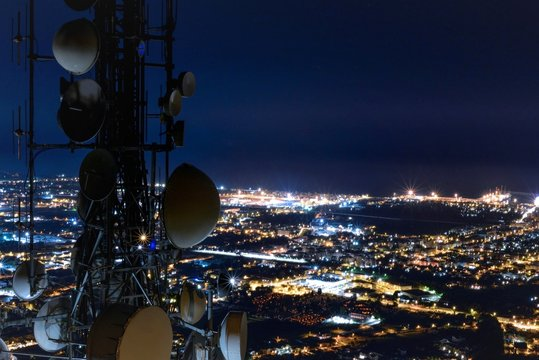 Telecommunications tower, antenna and satellite dish, network repeaters, base transceiver station and city at night as background. Copy space.