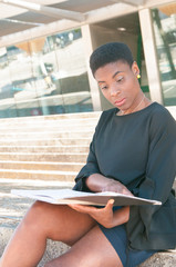 Focused pensive African American woman turning pages of photo book outside. Serious black lady sitting on outdoor stair and reading book. Leisure concept