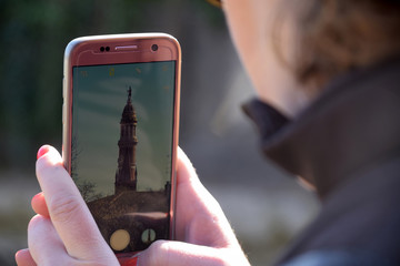 A tourist photographs the tower of the people in Palazzolo - Italy