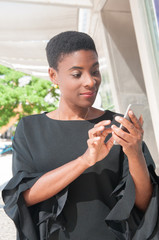 Cheerful African American woman using mobile app outdoors. Positive black lady texting message on phone. Wireless connection concept