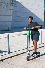 Content black woman riding electric scooter outdoors. Young woman wearing casual blouse and skirt with building in background. Modern transportation concept.