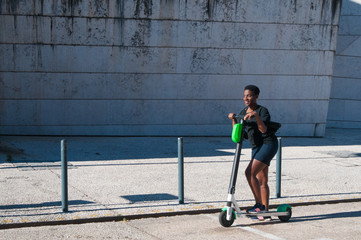 Smiling black woman standing on electric scooter outdoors. Young woman wearing casual blouse and skirt with building in background. Transportation technology concept.
