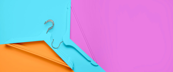 Creative fashion concept. Flat lay top view colored wooden hangers on blue pink orange neon...
