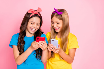 Portrait of cheerful kids laughing hold gadgets look funny information wear trendys tylish t-shirt headbands isolated over pink background