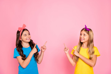 Portrait of two nice-looking attractive charming cute lovely confident content cheerful cheery pre-teen girls showing promotion advert ad isolated on pink pastel background