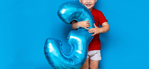 small cute blonde boy on blue background holding foil-coated sphere baloon blue colour. happy birthday three years old