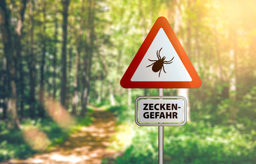 close-up of warning sign with text ZECKEN GEFAHR, German for beware of ticks, against defocused...