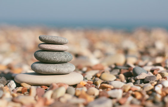 Stone zen pyramid on blurred beach background. Warm summer photo. Calm and rest place. Spa therapy background. Text space.