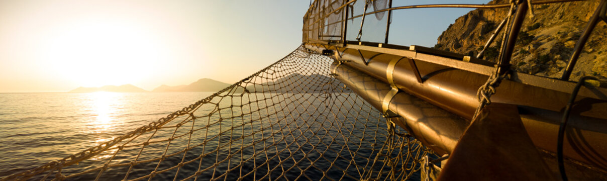 Sailing ship bow with netting heading out to see at sunset on turquoise water, Turkey panoramic